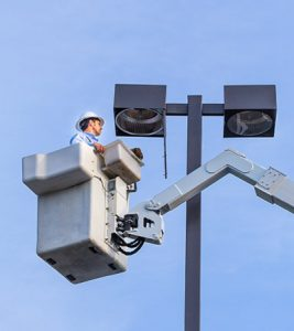 Man fixing light from bucket truck