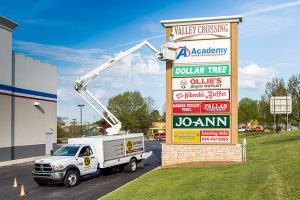 Man fixing Valley Crossing sign from bucket truck